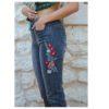 Detalle bordado flores rojas en jeans negros